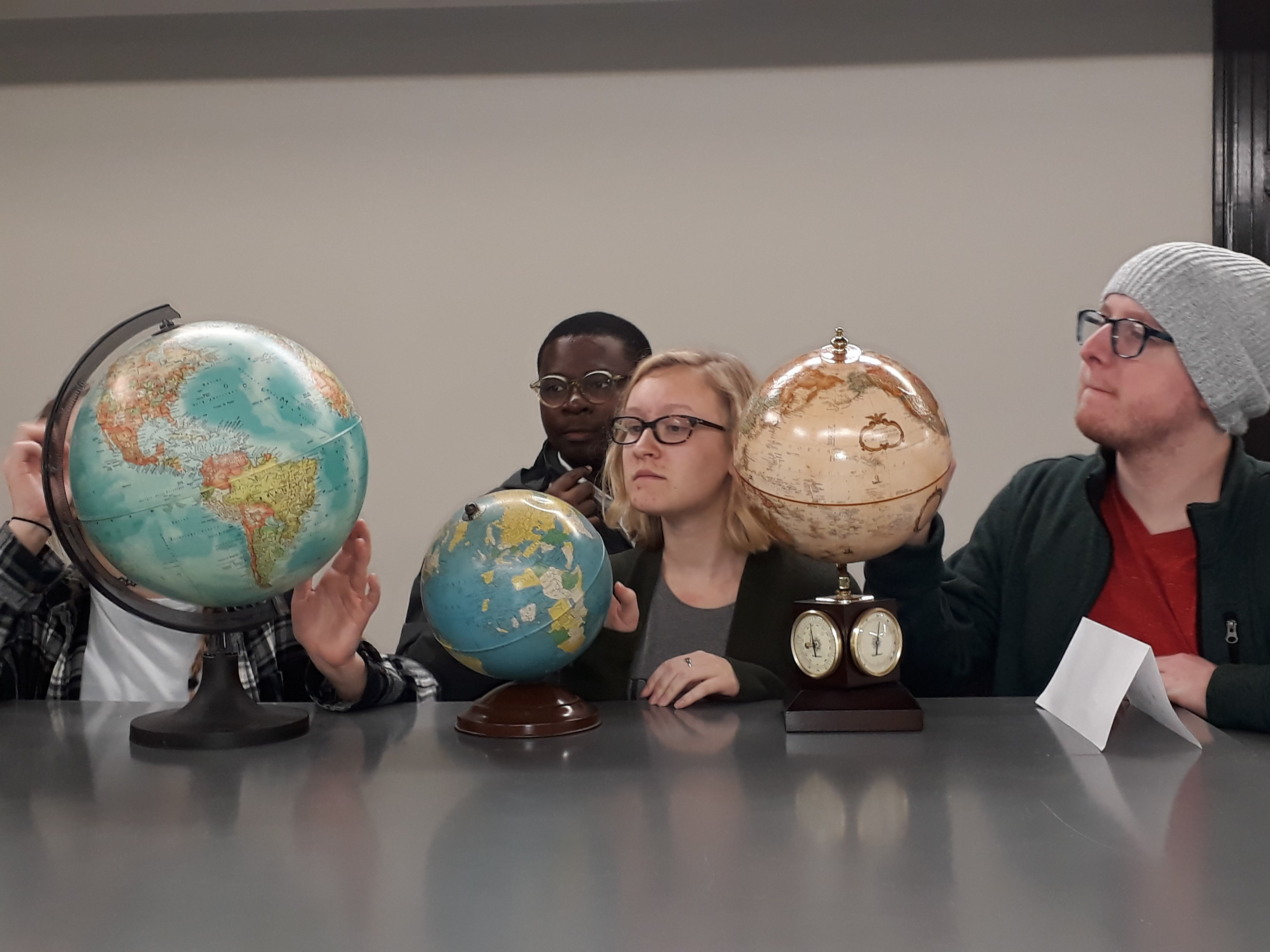 students examining different globes